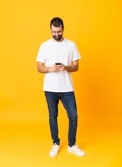Colpo integrale dell'uomo con la barba sopra giallo isolato che invia un messaggio con il cellulare