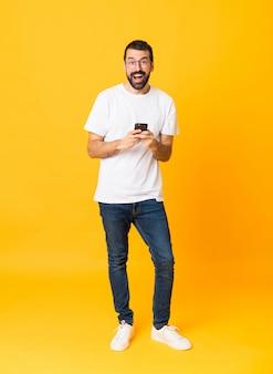 Colpo integrale dell'uomo con la barba sopra giallo isolato sorpreso e inviando un messaggio