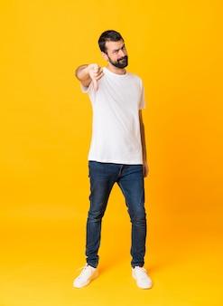 Colpo integrale dell'uomo con la barba sopra il pollice di mostra giallo isolato giù con l'espressione negativa