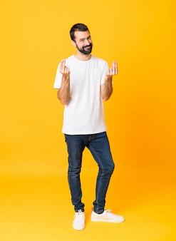 Colpo integrale dell'uomo con la barba sopra la parete gialla isolata che fa gesto dei soldi