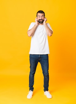 Colpo integrale dell'uomo con la barba sopra le orecchie frustrate e di copertura isolate gialle