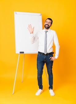 Colpo integrale dell'uomo d'affari che dà una presentazione sul bordo bianco che saluta con la mano con l'espressione felice