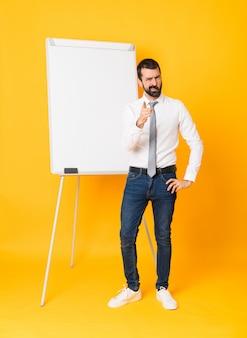 Colpo integrale dell'uomo d'affari che dà una presentazione sul bordo bianco sopra fondo giallo isolato frustrato e che indica la parte anteriore