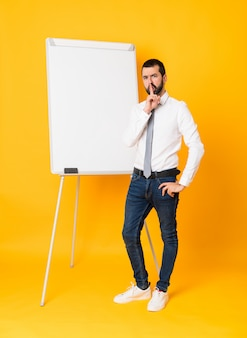 Colpo integrale dell'uomo d'affari che dà una presentazione sul bordo bianco sopra giallo isolato che mostra un segno di gesto di silenzio che mette il dito in bocca