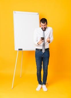 Colpo integrale dell'uomo d'affari che dà una presentazione sul bordo bianco sopra giallo isolato sorpreso e che invia un messaggio