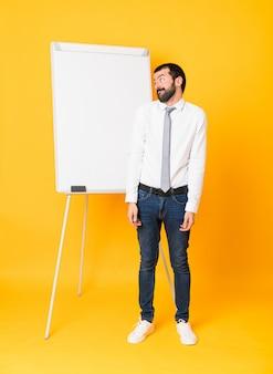 Colpo integrale dell'uomo d'affari che dà una presentazione sul bordo bianco sopra il gesto di fabbricazione giallo isolato di dubbi che guarda il lato
