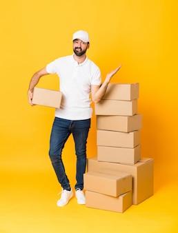 Colpo integrale dell'uomo di consegna fra le scatole sopra fondo giallo isolato insoddisfatto di non capire qualcosa