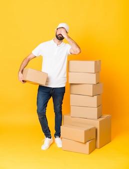Colpo integrale dell'uomo di consegna fra le scatole sopra gli occhi gialli isolati della copertura a mano.