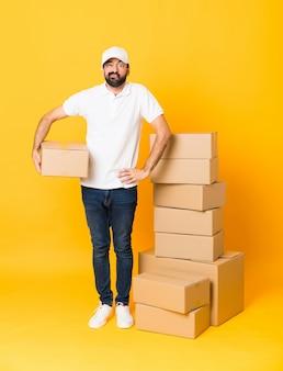 Colpo integrale dell'uomo di consegna fra le scatole sopra la sensibilità gialla isolata di sensibilità della parete turbata