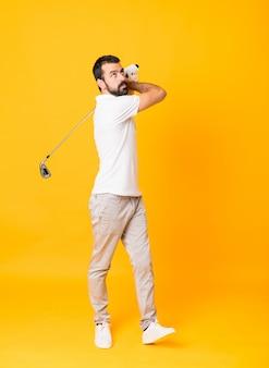Colpo integrale dell'uomo sopra fondo giallo isolato che gioca golf