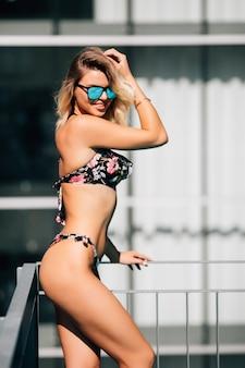 Colpo integrale di una giovane donna sottile in costume da bagno a bordo piscina.