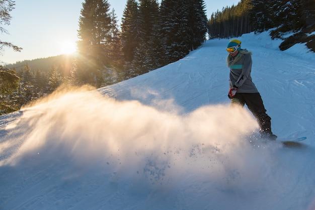 Colpo integrale di uno snowboarder della donna che guida pendio nevoso