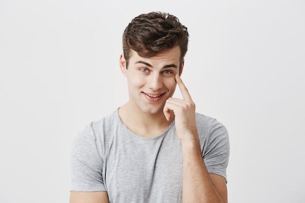 Colpo isolato di giovane ragazzo caucasico allegro felice che sembra soddisfatto, tenendo il dito sul suo tempio, essendo felice di ricevere grandi profitti dalle vendite, sorridendo con i denti, fiero di se stesso.