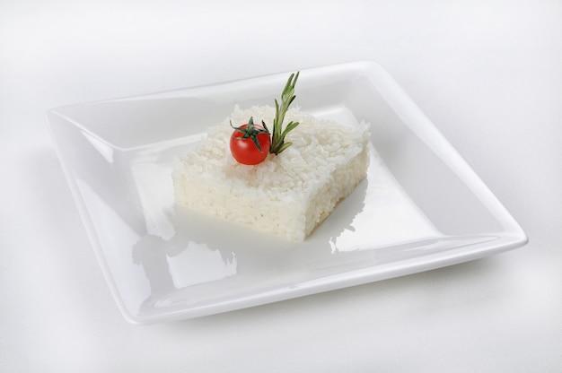 Colpo isolato di un riso a forma di quadrato su un piatto bianco
