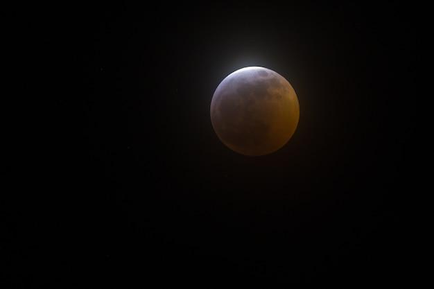 Colpo largo del primo piano di una luna piena su una priorità bassa nera