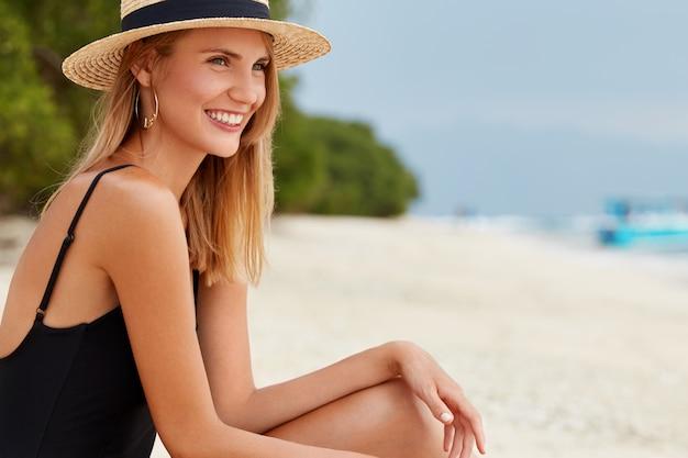 Colpo laterale di bella donna felice con pelle sana abbronzata, indossa costume da bagno e cappello di paglia, trascorre il tempo libero sulla spiaggia sabbiosa, soddisfatta di trascorrere le vacanze estive in un luogo paradisiaco