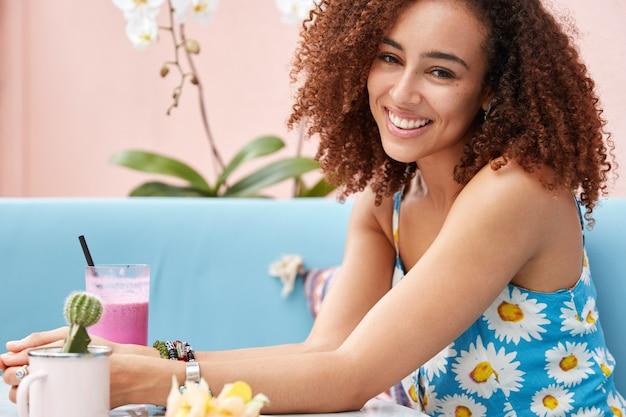 Colpo laterale di giovane donna sorridente attraente giovane con acconciatura afro, vestita con abiti estivi luminosi