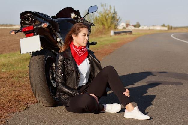 Colpo laterale di pensosa giovane motociclista con esperienza femminile indossa giacca di pelle, scarpe da ginnastica bianche, si siede vicino alla moto su asfalto