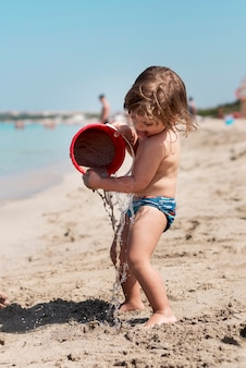 Colpo laterale di un bambino che gioca con il secchio di sabbia
