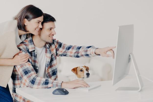 Colpo lateralmente della famiglia felice uso moderno computer per lo shopping online