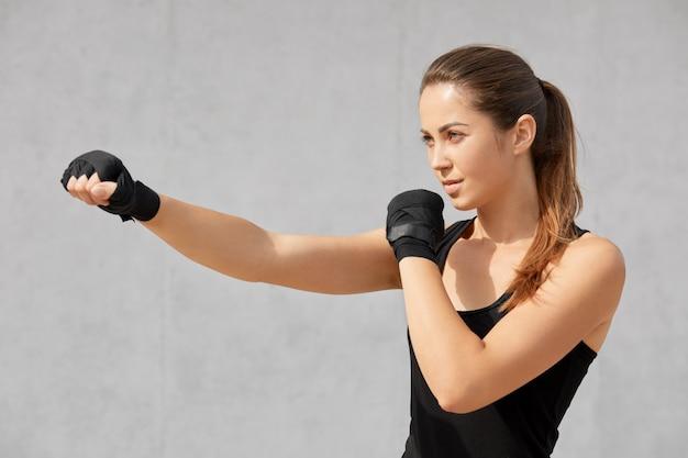 Colpo lateralmente di attraente donna sportiva pugile ha bende sulle mani