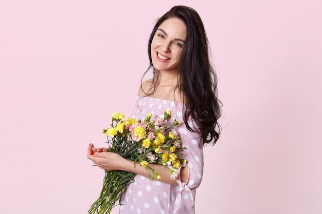 Colpo lateralmente di felice attraente giovane donna tiene fiori primaverili, vestito in abito a pois, posa sul rosa, ha un sorriso amichevole sul viso, ha una relazione romantica con il marito