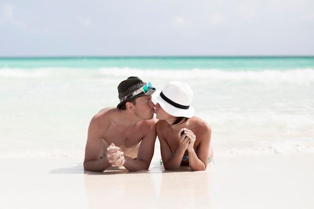 Colpo lungo baciare felice coppia in spiaggia