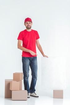 Colpo lungo del corriere circondato da scatole