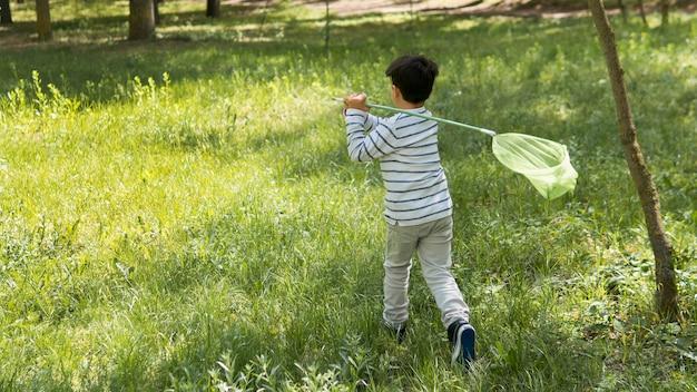 Colpo lungo del ragazzo che prova a catturare le farfalle