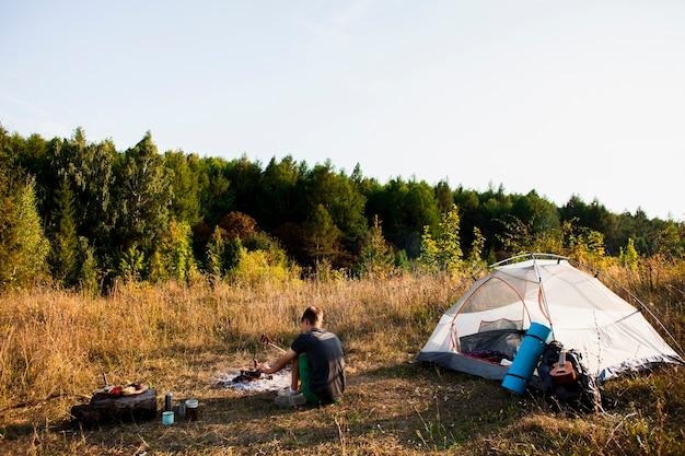Colpo lungo dell'uomo che esamina la foresta accanto alla sua tenda