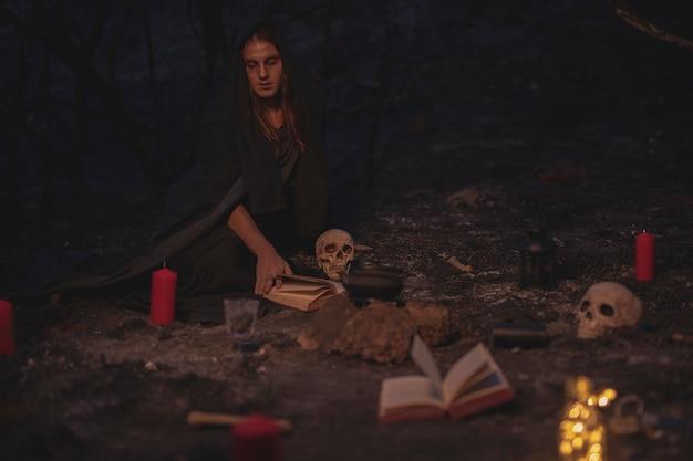 Colpo lungo della disposizione della stregoneria con il libro degli incantesimi e le candele