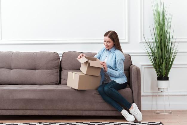 Colpo lungo della donna che apre una scatola