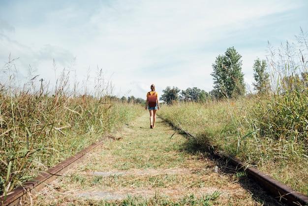 Colpo lungo della donna che cammina sulla ferrovia