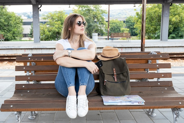 Colpo lungo della donna che si siede su un banco