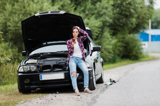 Colpo lungo della donna che si siede sull'automobile