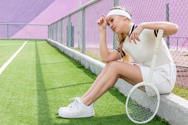 Colpo lungo della donna di tennis su un campo di tennis