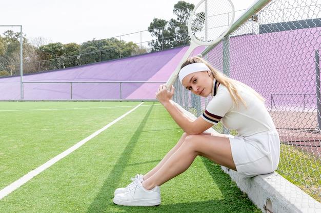 Colpo lungo della donna laterale che tiene il razzo di tennis