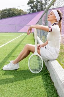 Colpo lungo della donna laterale di tennis su un campo di tennis