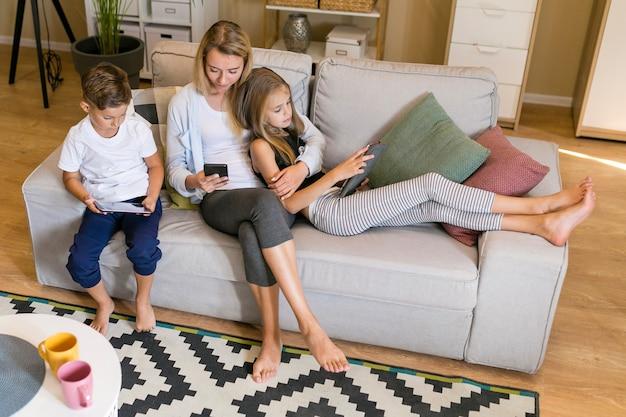Colpo lungo della madre e dei suoi figli seduti insieme guardando i telefoni