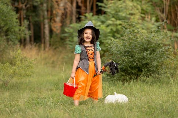 Colpo lungo della ragazza con il costume di halloween della strega in natura