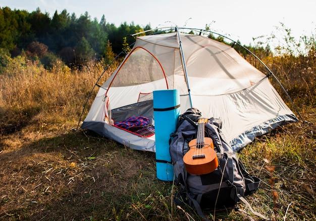 Colpo lungo della tenda bianca con bagagli e chitarra