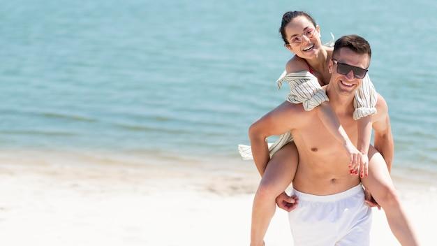 Colpo lungo delle coppie felici alla spiaggia