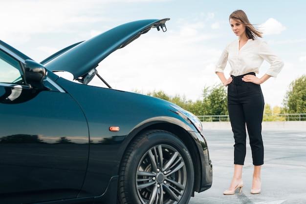 Colpo lungo di donna e auto