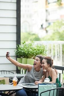 Colpo lungo di due ragazze che prendono selfie divertente in un caffè estivo