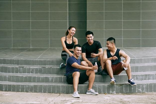 Colpo lungo di giovani amici in abiti sportivi che riposano sulle scale all'aperto e che ridono con gioia