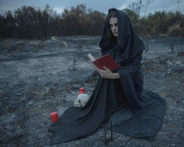 Colpo lungo di un mago maschio che si siede e che legge un libro