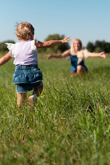 Colpo lungo di una bambina che corre a sua madre