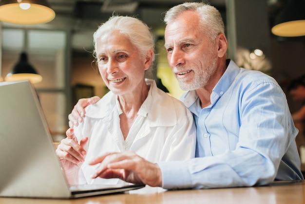 Colpo medio anziani con un computer portatile
