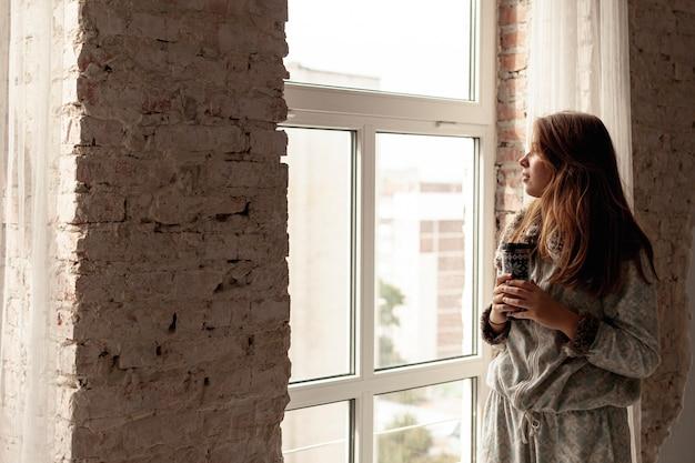 Colpo medio bella ragazza guardando fuori dalla finestra