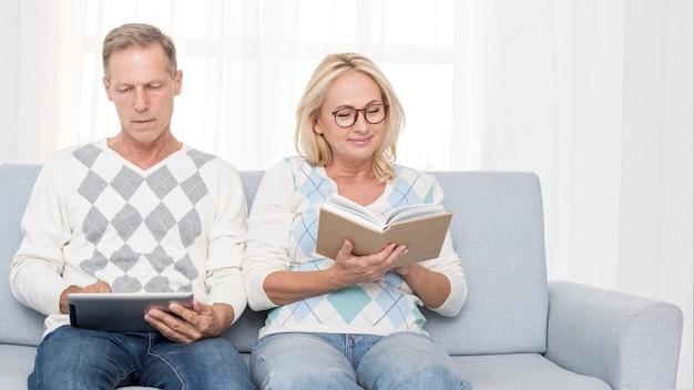 Colpo medio coppia sul divano a leggere